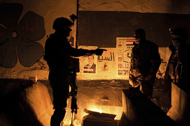 A fire illuminates election posters placed on a mural for the joint Iraqi Army and the Sons of Iraq checkpoint in Baghdad's Adhamiya district.