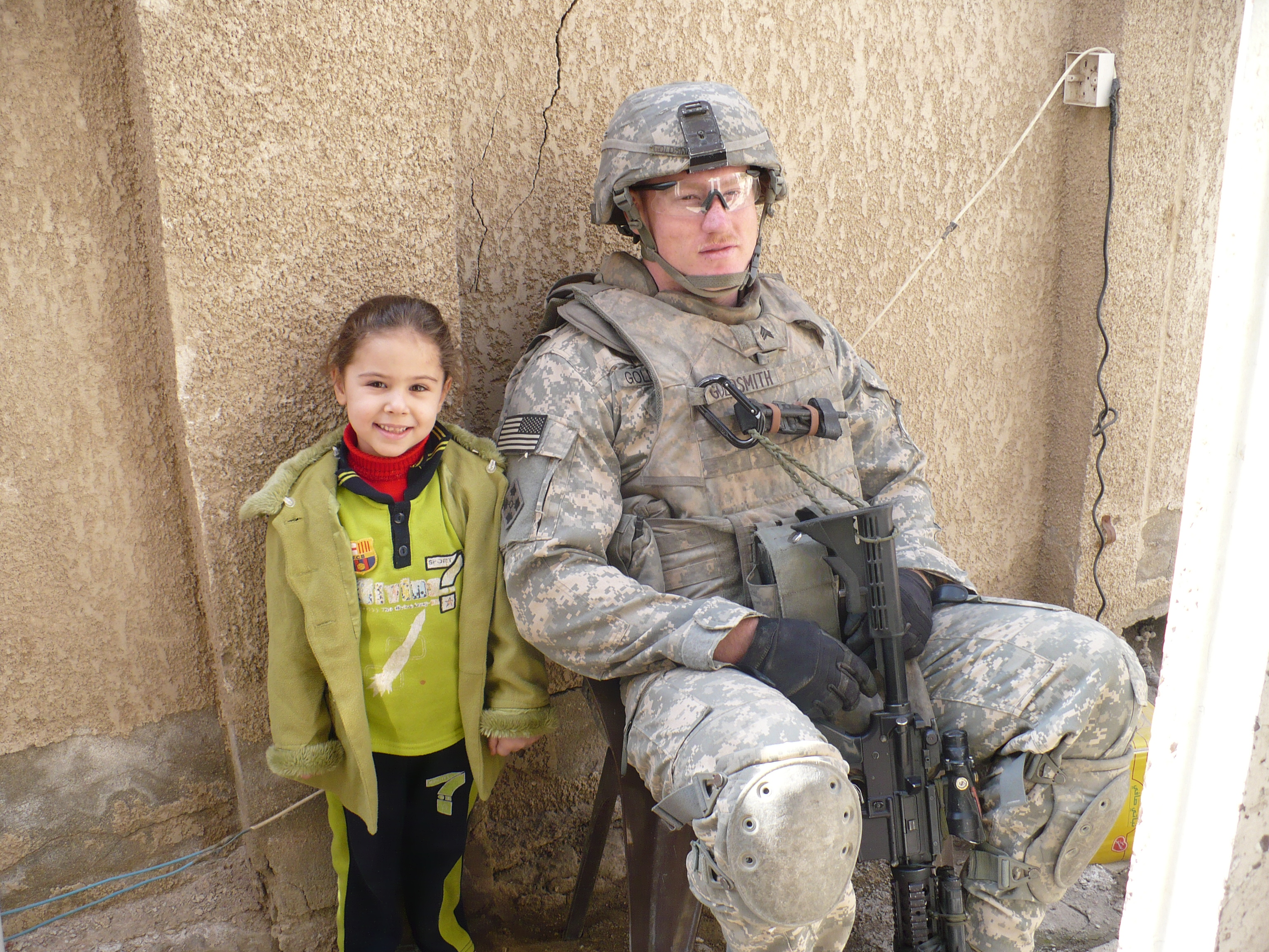 This cute little girl had no fear as the dozen armed and armored American soldiers entered her house to search for AK-47s. She followed us around and posed for this picture with the author.